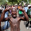 A man gestures as he celebrates in Bujumbura, Burundi May 13, 2015. Crowds poured onto the streets of Burundi's capital on Wednesday to celebrate after a general said he was dismissing President Pierre Nkurunziza for violating the constitution by seeking a third term in office, a Reuters witness said. REUTERS/Goran Tomasevic