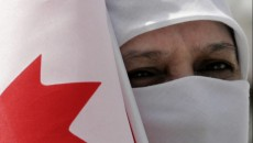 TORONTO,JULY.01.2005--Abida Saleem, of Pakistan, holds a Canadian flag as she watches her husband become a Canadian citizen at a swearing-in ceremony held at Centennial Park in Etobicoke Friday July 1, 2005. STAFF PHOTO: Brent Foster/National Post ADD: Canada Day  , citizenship , citizens , immigrants  , immigration  ,  muslim , burkha , burqa /pws