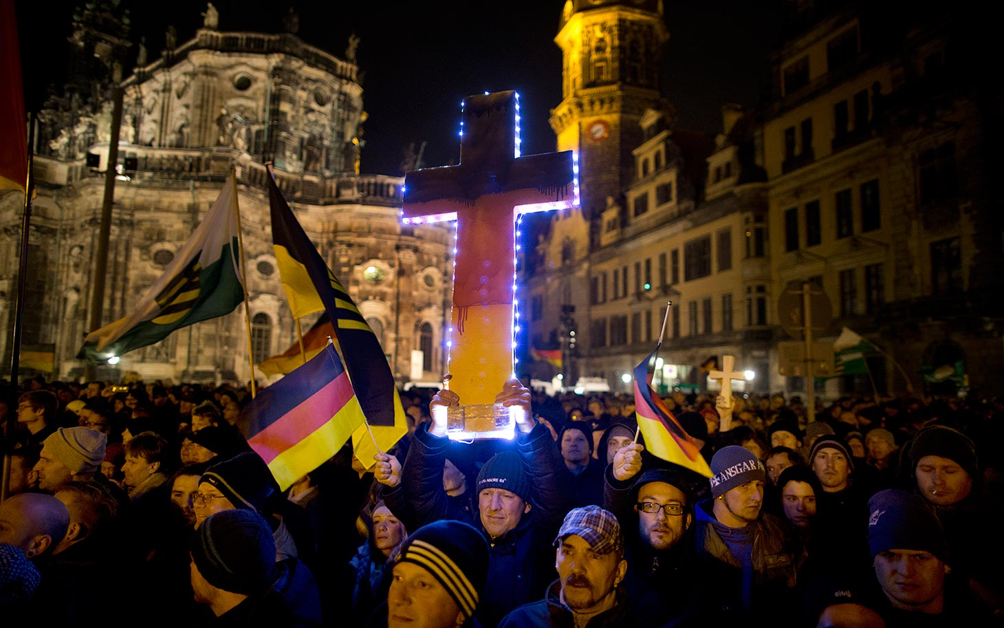 December 22, 2014 - Germany, Saxony, Dresden: A demonstrator holds a illuminated cross as he takes part in the demonstration of about 17,500 Supporters of the PEGIDA movement  at another of their weekly gatherings. Demonstrators shout slogans as: 'Luegenpresse' (Mendacious Press) and 'Wir sind das Volk (We are the people' the 1989 slogan of the GDR's peacefull freedom demonstrations). PEGIDA is an acronym for 'Patriotische Europaeer Gegen die Islamisierung des Abendlandes,' which translates to 'Patriotic Europeans Against the Islamification of the Occident' and has quickly gained a spreading mass appeal by demanding a more restrictive policy on Germany's acceptance of foreign refugees and asylum seekers. Parts of this  right-wing movement is also against the Euro and the Western liberal style of living in general. The first PEGIDA march took place in Dresden in October and has since attracted thousands of participants to its weekly gatherings that have also begun spreading to other cities in Germany. (Hermann BredehorstPolaris)